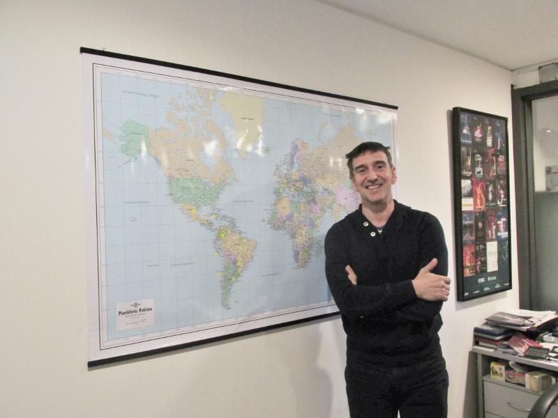 Con risa y orgullo a la vez, el director posa junto a un planisferio que señala los puntos del planeta que han tocado con las giras. Foto: Laura Chertkoff.