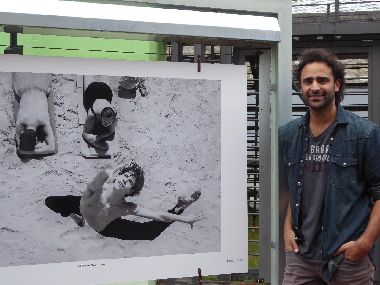 Santiago Barreiro junto a una de sus fotos que muestra a Ciro Tamayo en uno de sus saltos y a una vecina de Montevideo en una de sus sorpresas. Gentileza Tanya Campos.